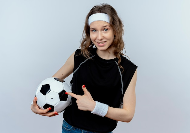 흰색 벽 위에 유쾌하게 서 웃고 그것에 손가락으로 축구 공 pointign을 들고 머리띠와 검은 운동복에 젊은 피트니스 소녀