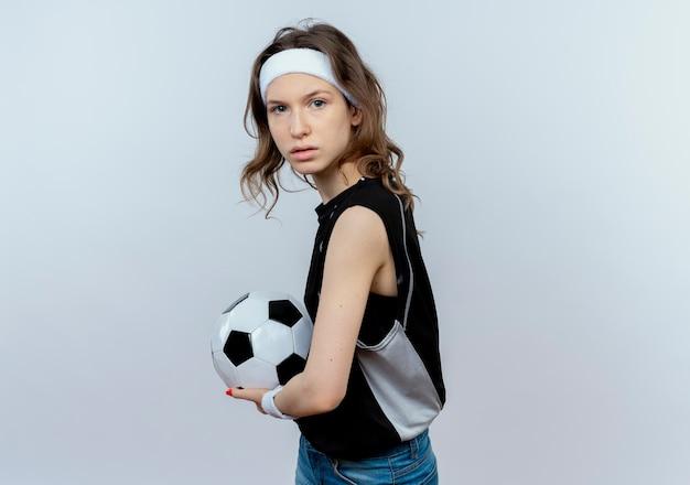 흰색 벽 위에 서 심각한 얼굴로 축구 공을 들고 머리띠와 검은 운동복에 젊은 피트니스 소녀