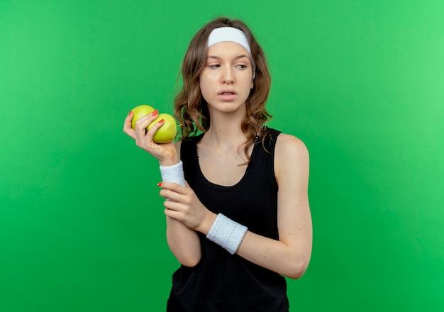 Молодая фитнес-девушка в черной спортивной одежде с повязкой на голове держит два зеленых яблока, скептически глядя в сторону, стоя у зеленой стены