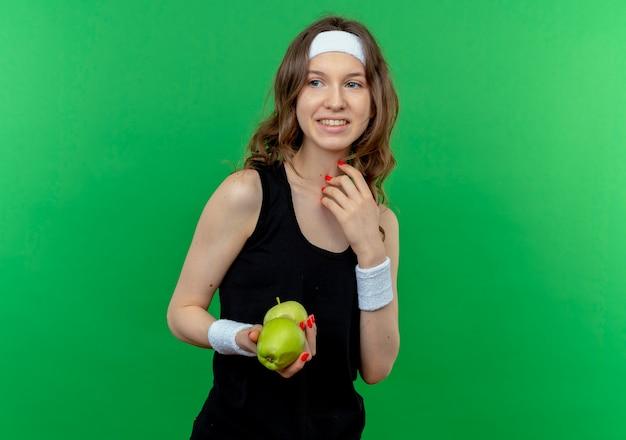 Молодая фитнес-девушка в черной спортивной одежде с повязкой на голову держит два зеленых яблока, весело улыбаясь, стоя над зеленой стеной