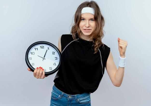 白い壁の上に立っている自信を持って握りこぶしを笑顔で壁時計を保持しているヘッドバンドと黒のスポーツウェアの若いフィットネスの女の子