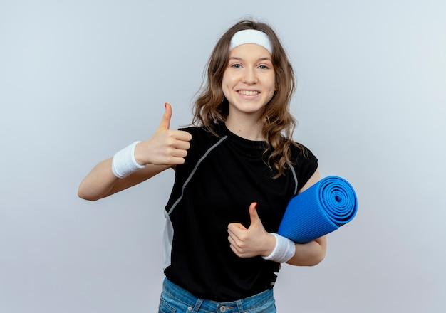 흰색 벽 위에 서 엄지 손가락을 보여주는 행복 afce 미소 요가 매트를 들고 머리띠와 검은 운동복에 젊은 피트니스 소녀