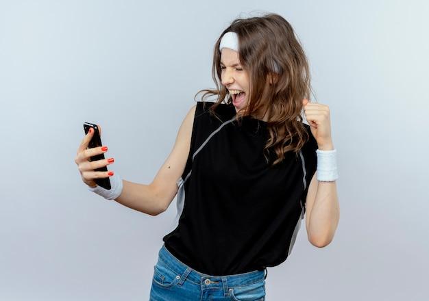 白い壁の上に立っている彼女のスマートフォンの幸せで興奮した握りこぶしの画面を見ているヘッドバンドを持つ黒いスポーツウェアの若いフィットネスの女の子