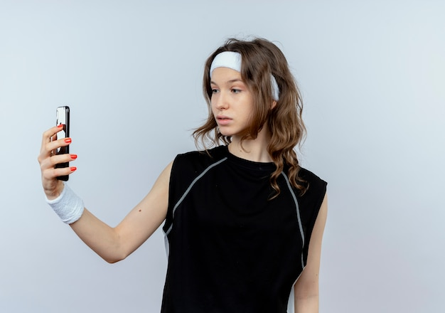 白い壁の上に立っている懐疑的な表情でスマートフォンの画面を見ているヘッドバンドと黒のスポーツウェアの若いフィットネスの女の子