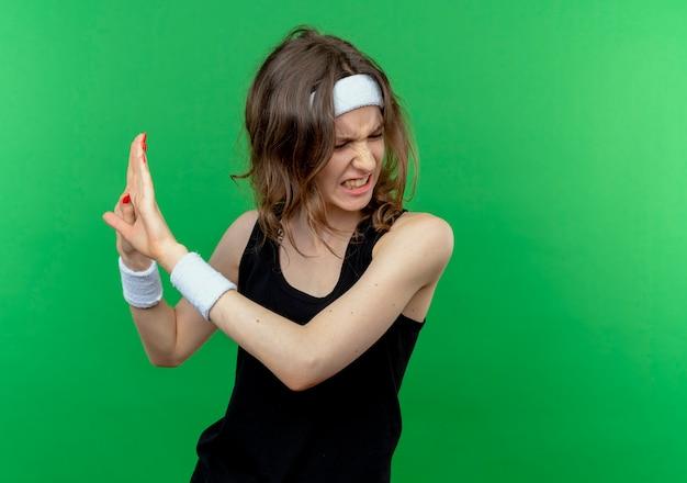 녹색 벽 위에 서서 가까이 서지 말라고 말하면서 머리띠가 손으로 손으로 방어 제스처를 만드는 검은 운동복에 젊은 피트니스 소녀