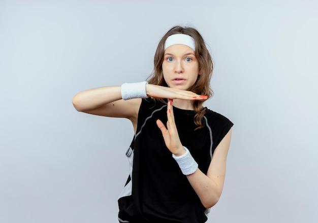 Молодая фитнес-девушка в черной спортивной одежде с повязкой на голову, делая жест тайм-аута, стоя над белой стеной