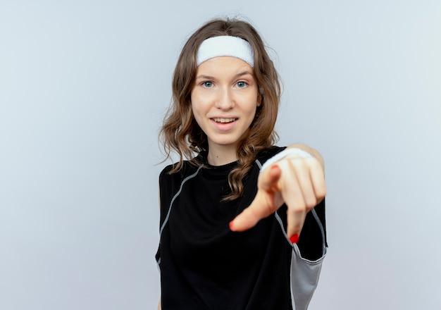 흰색 벽 위에 서 웃 고 손가락으로 가리키는 머리띠와 검은 운동복에 젊은 피트 니스 소녀