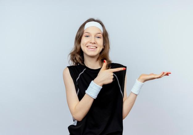 白い壁の上に立って笑顔の手の腕で何かを提示する側に指で指しているヘッドバンドを持つ黒いスポーツウェアの若いフィットネスの女の子