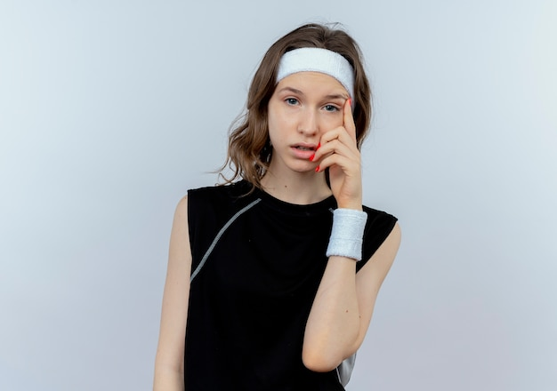 머리띠와 검은 운동복에 젊은 피트니스 소녀는 흰 벽 위에 서 의아해