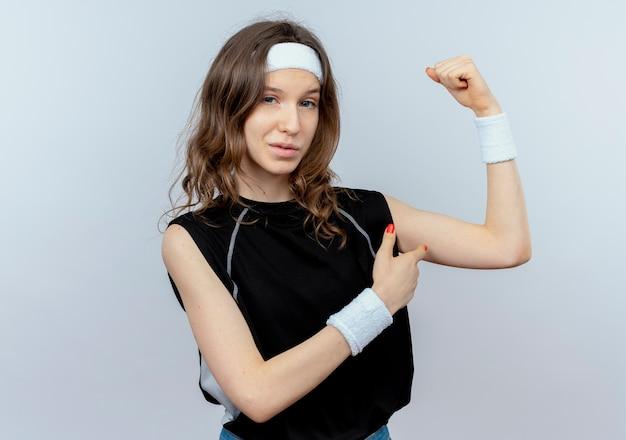 흰색 벽 위에 팔뚝 모양 자신감 서 보여주는 머리띠 손을 올리는 검은 운동복에 젊은 피트니스 소녀