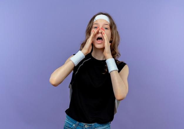 Молодая фитнес-девушка в черной спортивной одежде с повязкой на голове кричит или зовет руками возле рта, стоя над синей стеной