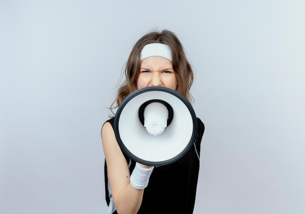흰 벽 위에 서있는 공격적인 표정으로 확성기로 외치는 머리띠와 검은 운동복에 젊은 피트니스 소녀