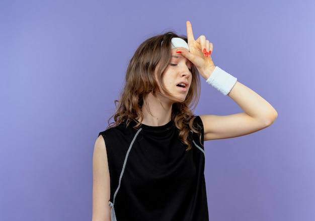 青の上で混乱しているように見える敗者が頭の上で歌うことを示すヘッドバンドを持つ黒いスポーツウェアの若いフィットネスの女の子