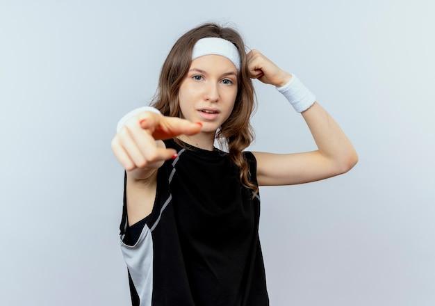 흰 벽 위에 서있는 팔뚝을 보여주는 주먹을 올리는 손가락으로 가리키는 자신감 식으로 머리띠와 검은 색 운동복에 젊은 피트니스 소녀