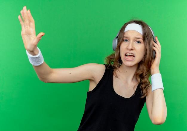 緑の壁の上に立っている手で一時停止の標識を作る混乱と不満に見えるヘッドフォン付きのヘッドバンドと黒のスポーツウェアの若いフィットネスの女の子