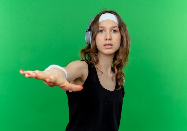緑の壁の上に立っている手で落ち着いたジェスチャーをするヘッドフォン付きのヘッドバンドと黒のスポーツウェアの若いフィットネスの女の子