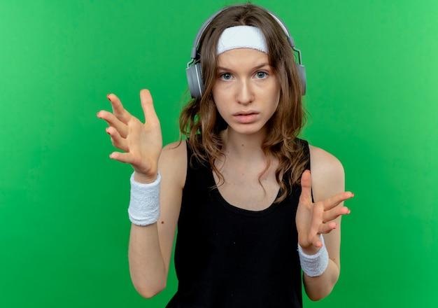녹색 벽 위에 서있는 손으로 몸짓 심각한 얼굴로 헤드폰 머리띠와 검은 운동복에 젊은 피트니스 소녀