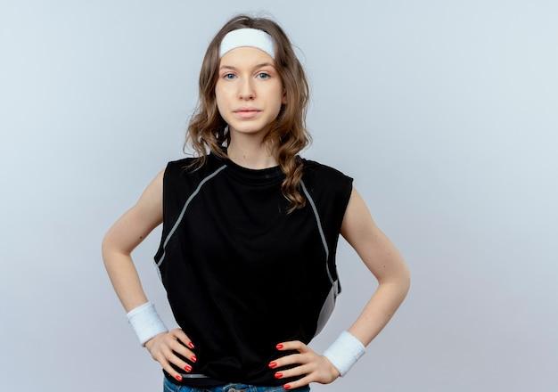 흰색 벽 위에 서 심각한 자신감 식으로 머리띠와 검은 운동복에 젊은 피트니스 소녀