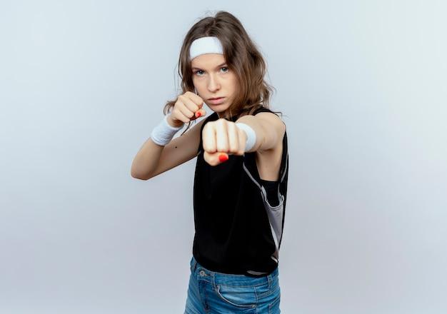 흰 벽 위에 서있는 떨리는 주먹으로 권투 선수처럼 포즈를 취하는 심각한 얼굴로 머리띠와 검은 색 운동복에 젊은 피트니스 소녀