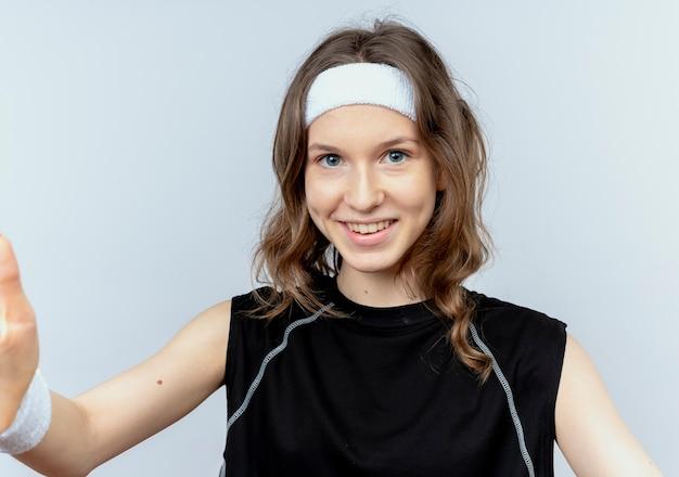흰 벽 위에 서있는 팔을 교차 심각한 얼굴로 머리띠와 검은 색 운동복에 젊은 피트니스 소녀