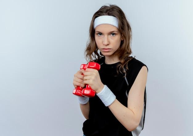 흰색 벽 위에 자신감 서 찾고 아령으로 운동 머리띠와 검은 운동복에 젊은 피트니스 소녀