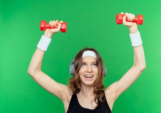 녹색 벽 위에 유쾌하게 서있는 아령으로 운동하는 머리띠와 검은 운동복에 젊은 피트니스 소녀