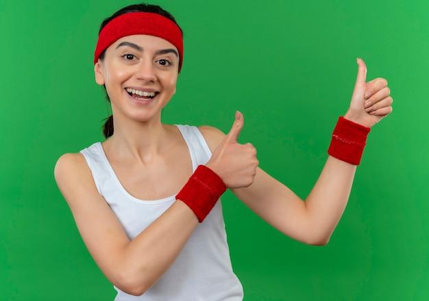 머리띠 행복하고 긍정적 인 웃고 녹색 벽 위에 서 엄지 손가락을 유쾌하게 보여주는 운동복에 젊은 피트니스 소녀