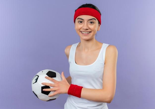 보라색 벽에 자신감이 행복하고 긍정적 인 서 웃고 축구 공을 들고 머리띠와 운동복에 젊은 피트니스 소녀