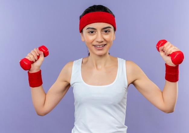 Молодая фитнес-девушка в спортивной одежде с повязкой на голову, держащая две гантели в поднятых руках, весело улыбаясь, делая упражнения, стоя над фиолетовой стеной