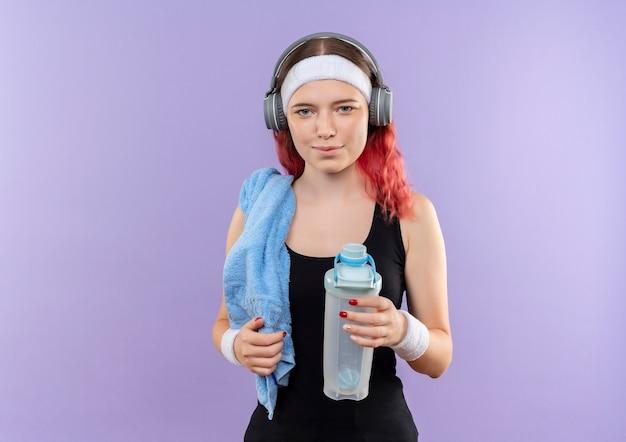 彼女の頭にヘッドフォンと彼女の首にタオルで紫色の壁の上に立って笑顔の水のボトルを保持しているスポーツウェアの若いフィットネスの女の子