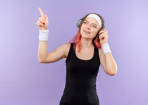 Молодая фитнес-девушка в спортивной одежде с наушниками на голове улыбается, указывая пальцем в сторону, стоящую над фиолетовой стеной