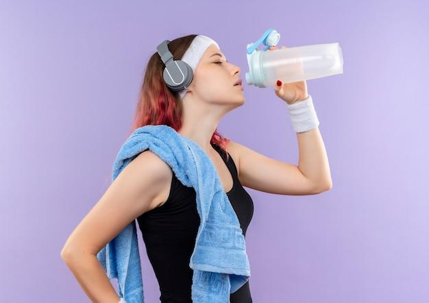 보라색 벽 위에 옆으로 서있는 그녀의 목 마시는 물에 수건으로 운동복에 젊은 피트니스 소녀