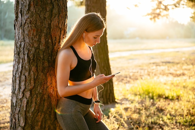 Young fitness girl listening to music in earphones and using a smartphone
