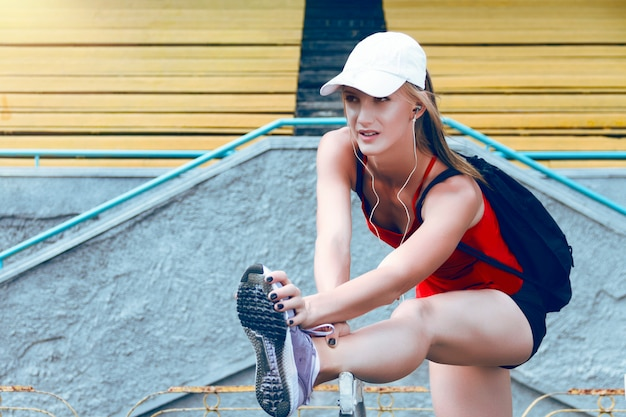 Young fitness girl listening to music and making exercises preparing for run on stadium