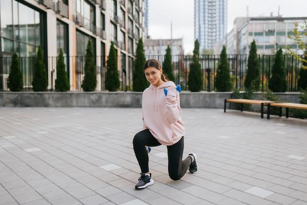 도시 공원에서 아령으로 운동을 하는 젊은 피트니스 소녀