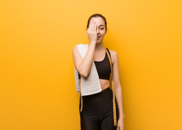 Young fitness girl shouting happy and covering face with hand