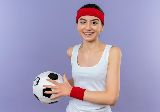 Young fitness girl in sportswear with headband holding soccer ball smiling confident happy and positive standing over purple wall