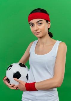 Giovane ragazza di forma fisica in abiti sportivi con fascia tenendo il pallone da calcio con espressione fiduciosa in piedi sopra la parete verde
