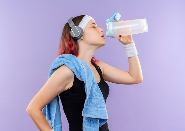 Young fitness girl in sportswear with towel on her neck drinking water standing sideways over purple wall