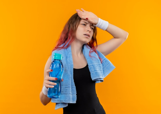 Young fitness girl in sportswear with towel on her neck holding bottle of water looking unwell touching her head standing over orange wall