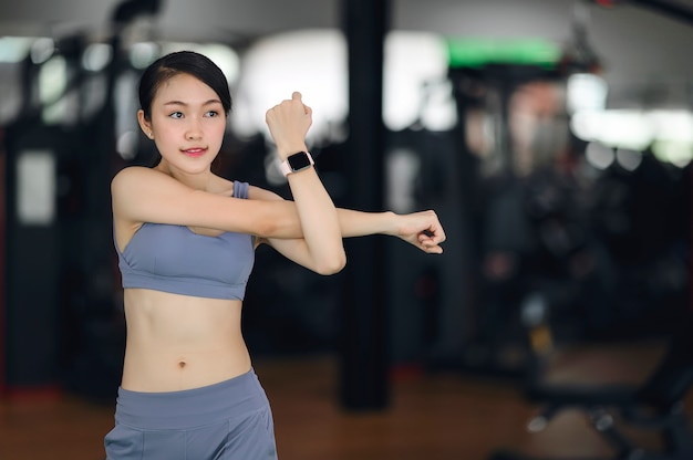Young fitness girl in stylish sportswear warming up before training in the gym