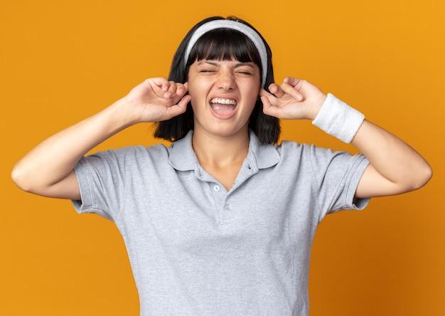 주황색 배경 위에 서 있는 짜증난 표정으로 손가락으로 귀를 막고 있는 머리띠를 한 젊은 피트니스 소녀