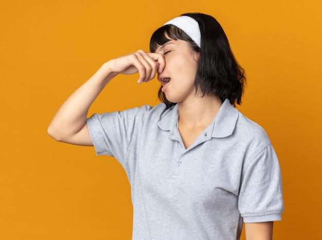 Giovane ragazza fitness che indossa la fascia che si chiude il naso con le dita che soffrono di puzza in piedi sopra l'arancia