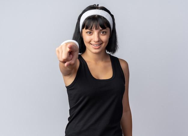 머리띠를 한 젊은 피트니스 소녀는 흰색 배경 위에 서 있는 카메라를 검지 손가락으로 가리키며 행복하고 자신감을 갖고 있습니다.