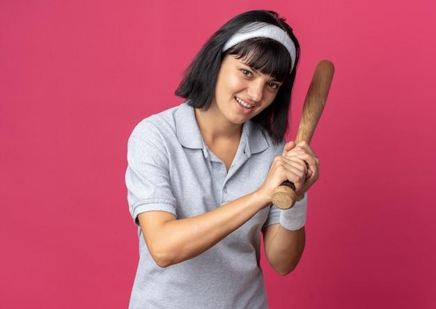 야구 방망이를 들고 머리띠를 한 젊은 피트니스 소녀가 분홍색 배경 위에 서서 카메라를 바라보며 행복하고 긍정적인 미소를 짓고 있습니다.