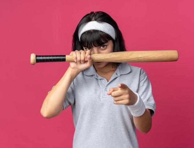 분홍색 배경 위에 서 있는 카메라를 검지 손가락으로 가리키는 자신감 있는 미소로 카메라를 바라보는 야구 방망이를 들고 머리띠를 한 젊은 피트니스 소녀