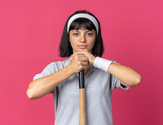 심각한 자신감 표정으로 카메라를보고 야구 방망이를 들고 머리띠를 착용하는 젊은 피트니스 소녀