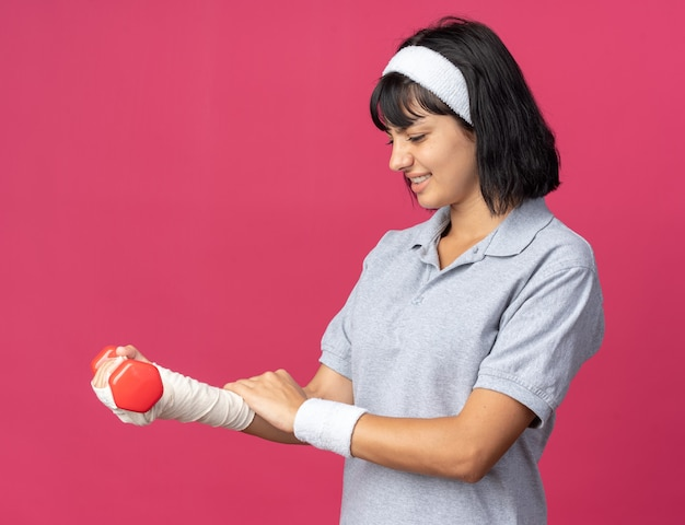 Young fitness girl wearing headband holding dumbbell in her bandaged hand feeling discomfort and pain standing over pink