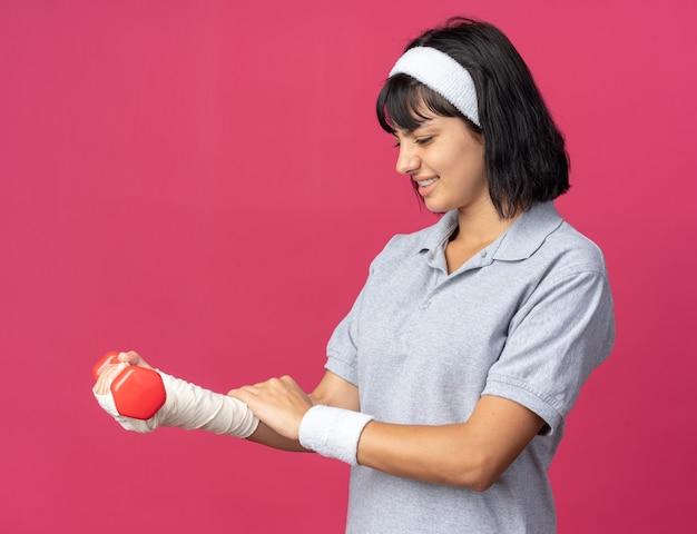 ピンクの上に立っている不快感と痛みを感じている彼女の包帯の手にダンベルを保持しているヘッドバンドを身に着けている若いフィットネスの女の子