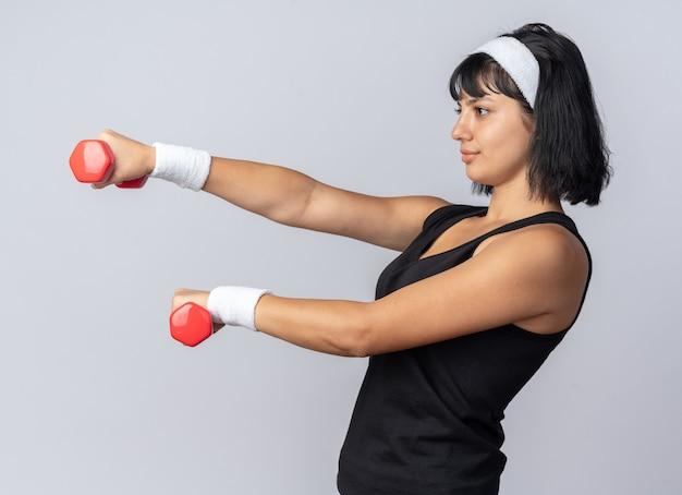 Giovane ragazza di forma fisica che indossa la fascia tenendo i manubri facendo esercizi che sembrano fiduciosi in piedi su sfondo bianco
